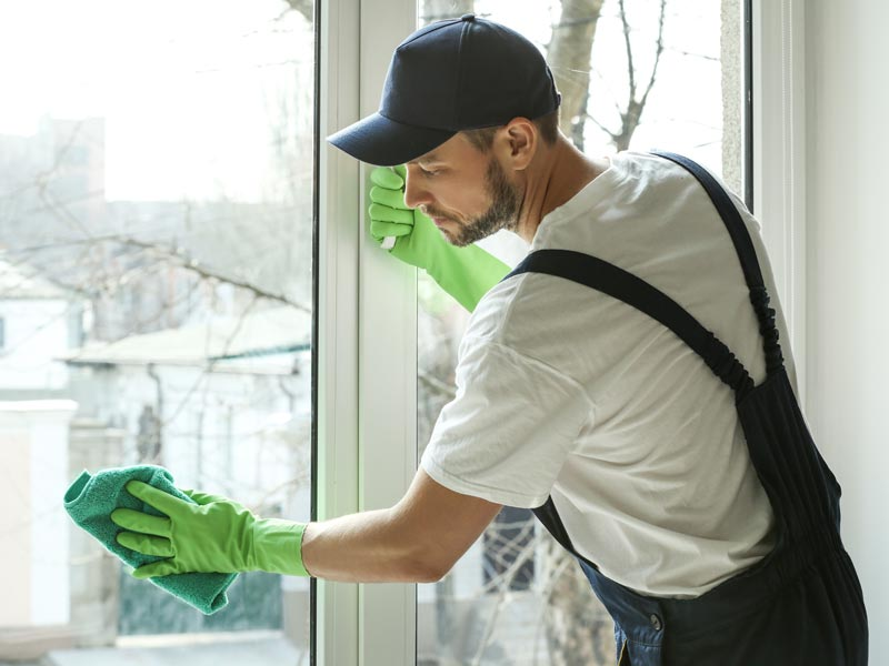 bigstock-Young-man-cleaning-window-in-o-181263898